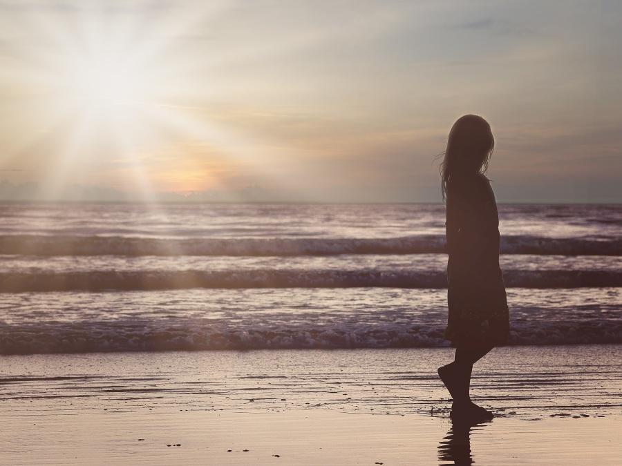 フリー 写真夕暮れの砂浜を歩く女の子