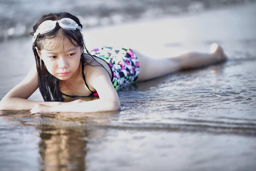 フリー 写真波打ち際で腹這い姿の女の子