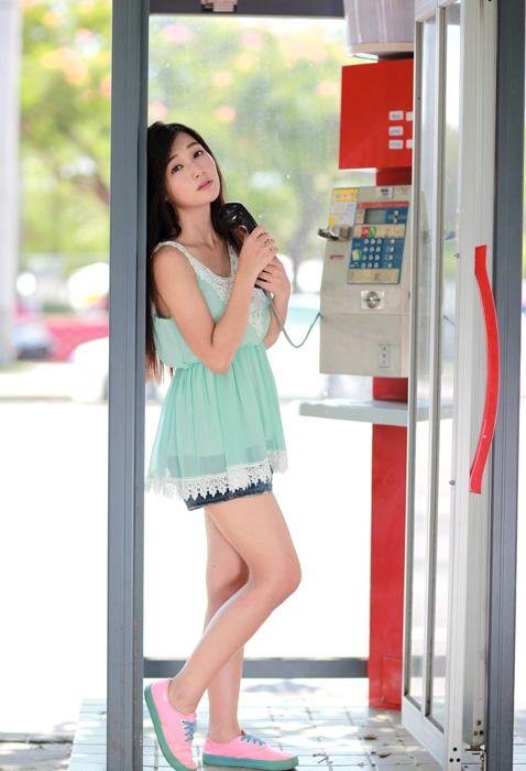 フリー 写真公衆電話の受話器を持つ女性
