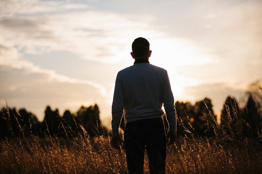 フリー 写真夕暮れの草むらに立つ外国人男性の後ろ姿