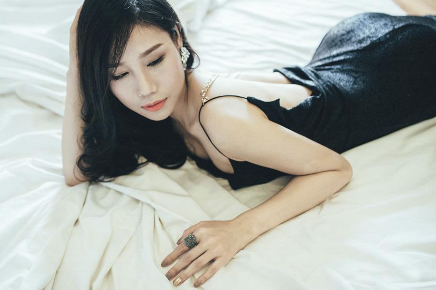 フリー 写真ドレス姿でベッドの上に腹ばいになる女性