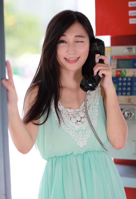フリー 写真公衆電話で舌を出しながらウインクする女性