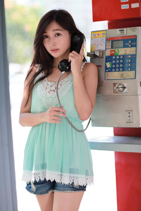 フリー 写真公衆電話の受話器を耳に当てる女性