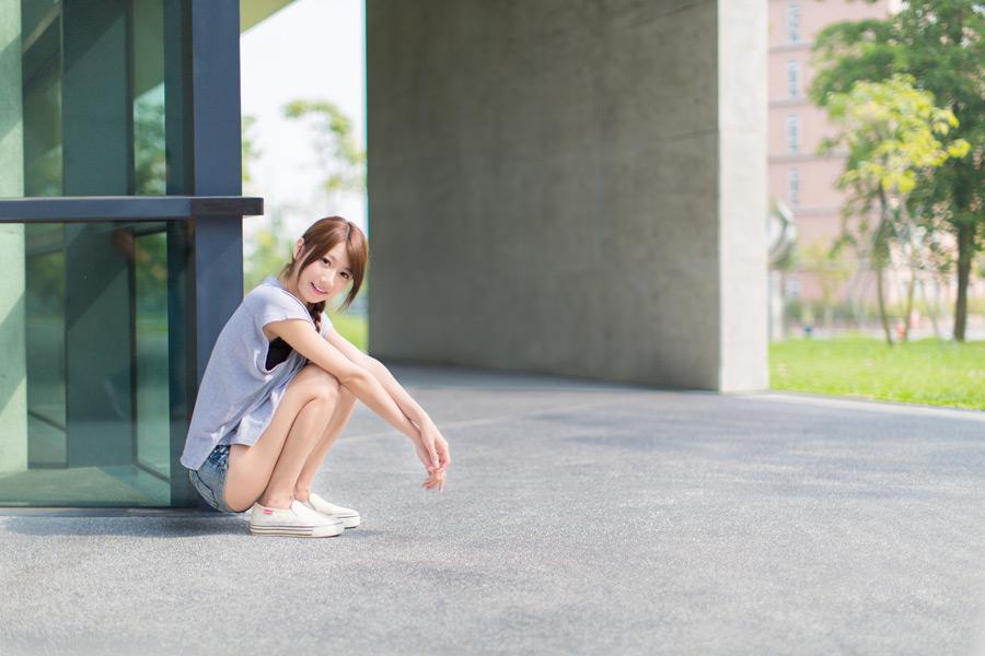 フリー 写真Tシャツとショートパンツ姿で建物の角にしゃがむ女性
