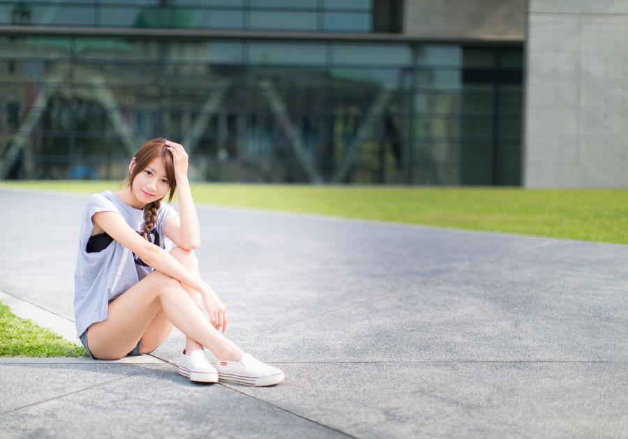 フリー 写真頭に手を当てて地面に座る女性ポートレイト