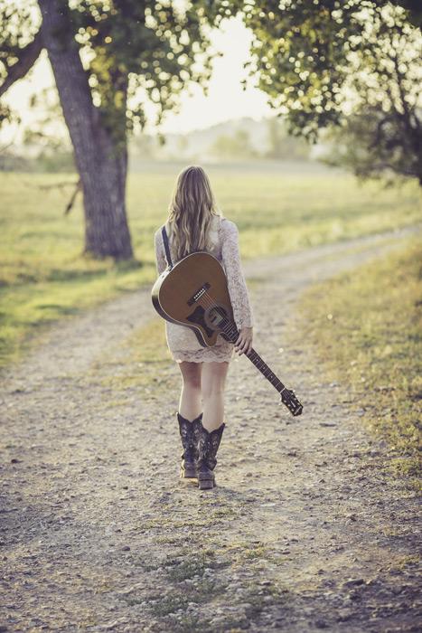 フリー写真 ギターを肩にかけて小道を歩く女性