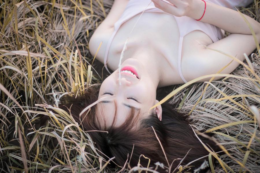 フリー写真 枯れた草むらの上で寝転ぶ女性