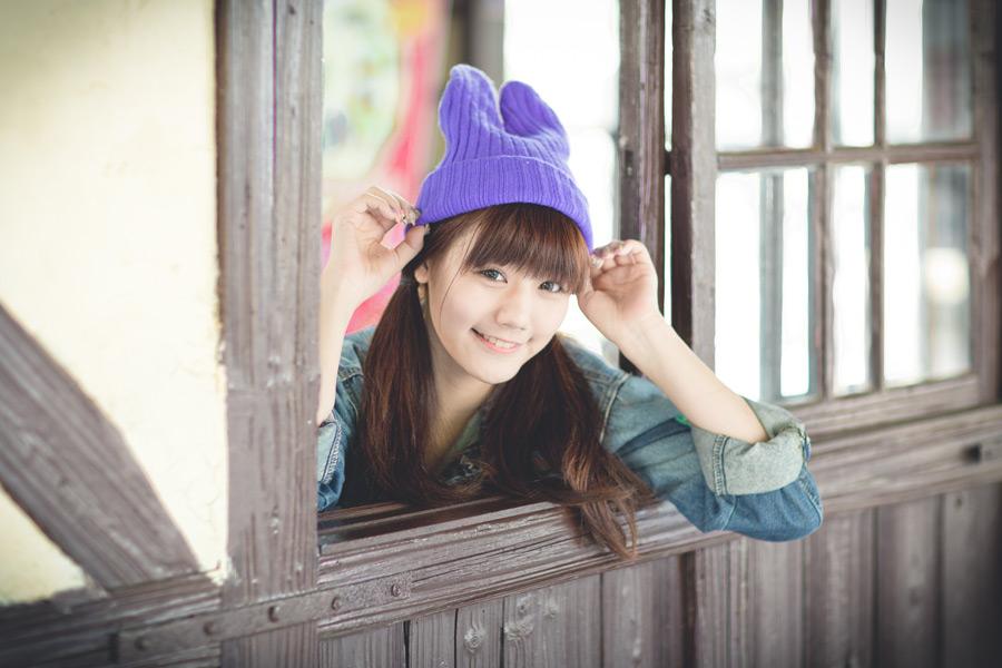 フリー写真 ニット帽を被って窓に寄りかかる女性のポートレイト