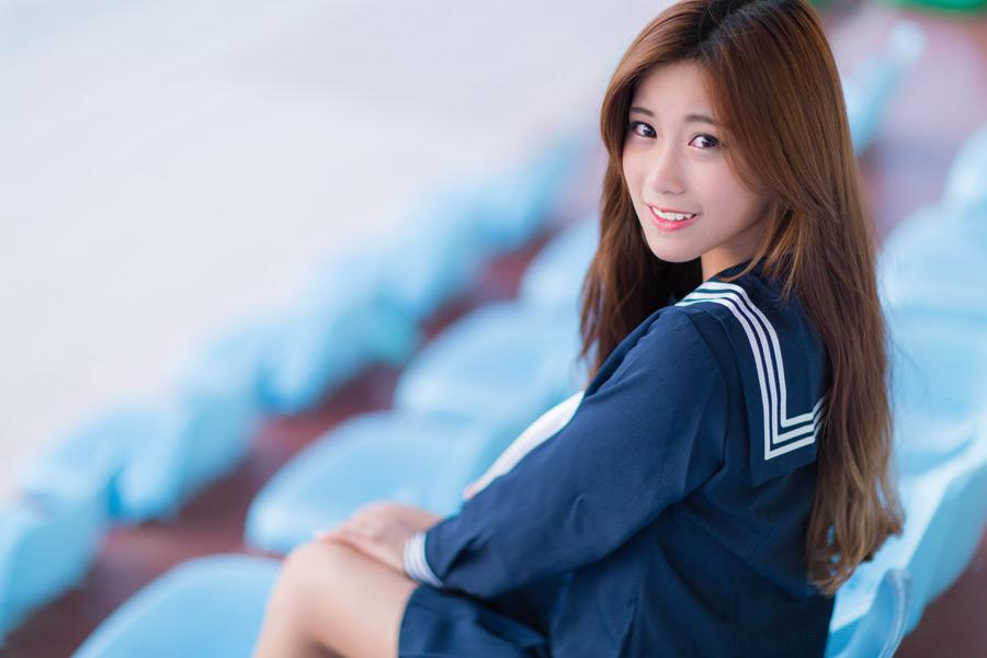 フリー写真 セーラー服姿で野球のスタンドに座る女子高生のポートレイト