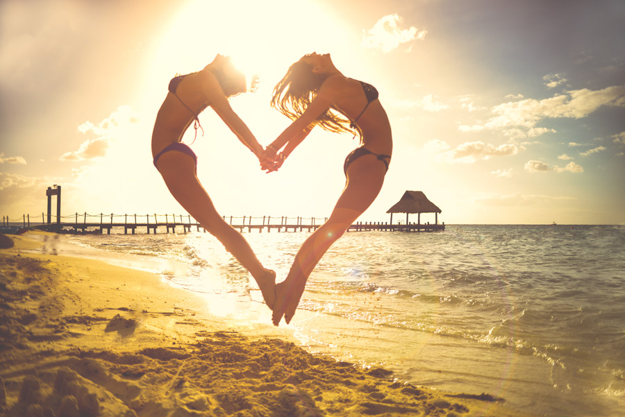 フリー写真 夕暮れのビーチでジャンプしてハートを作る二人の女性