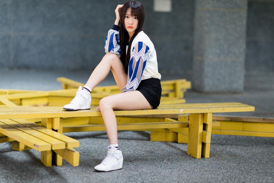 フリー写真 ベンチの上で膝を立てて座る女性のポートレイト