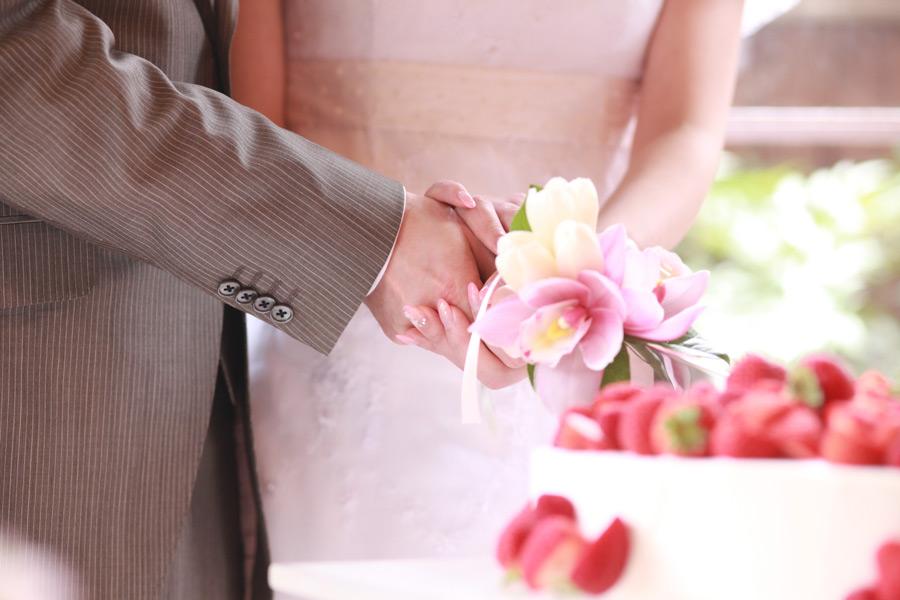 フリー写真 結婚式でケーキカットする新郎新婦