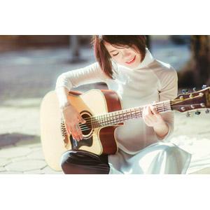 フリー写真, 人物, 女性, アジア人女性, ベトナム人, 女性(00068), アオザイ, ショートヘア, 音楽, 楽器, 弦楽器, ギター, アコースティックギター, 演奏する, 座る(地面), あぐらをかく
