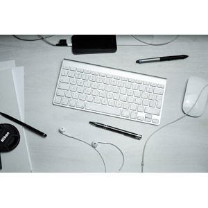 フリー写真, 机(デスク), キーボード, マウス, ボールペン, レンズキャップ, スマートフォン(スマホ), イヤホン(イヤフォン)
