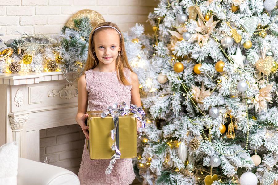 フリー写真 ツリーの横でクリスマスプレゼンを持つ女の子