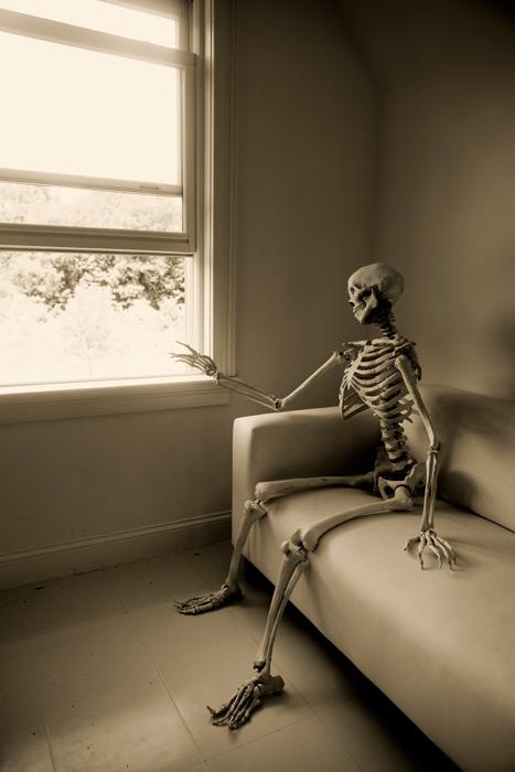 フリー写真 ソファーに座って帰りを待ち続ける骸骨