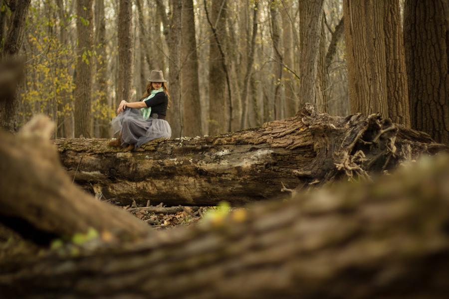 フリー写真 大きな倒木の上に座る外国人女性