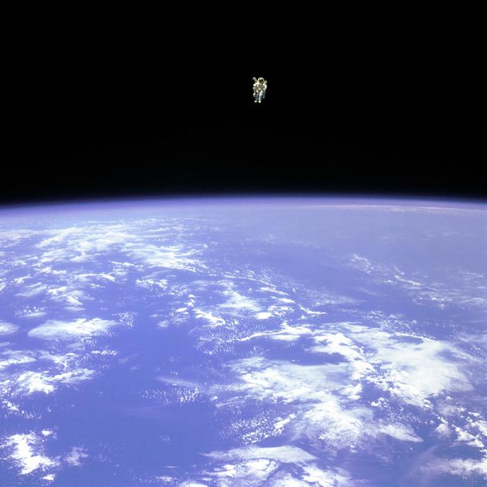 フリー写真 地球と宇宙遊泳する宇宙飛行士