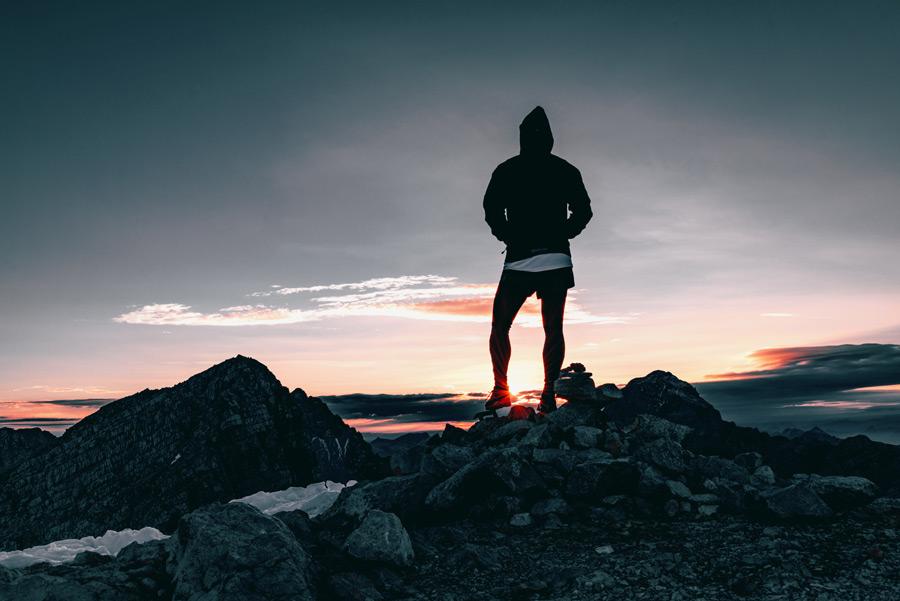 フリー写真 夕陽と岩の上に立つ人物の後ろ姿