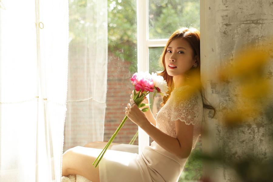 フリー写真 花を持って窓辺に腰掛ける女性