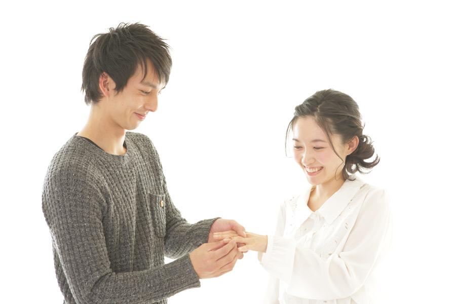 フリー写真 彼女の指に婚約指輪をはめる彼氏