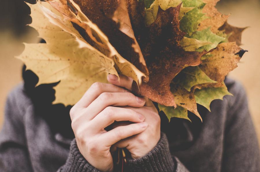 フリー写真 落ち葉で顔を隠す人物