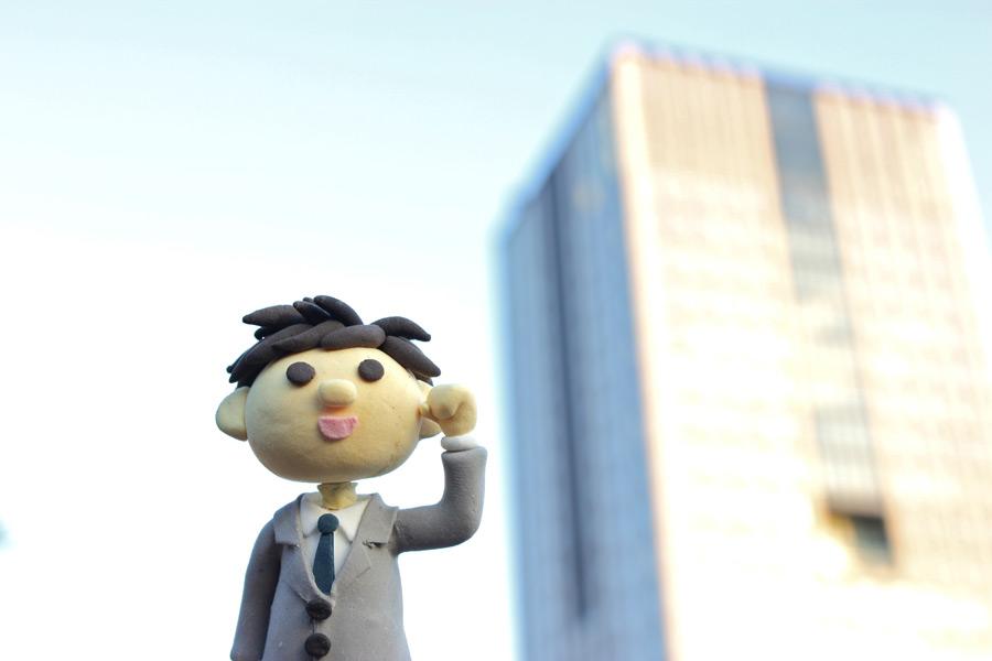 フリー写真 オフィスビルとサラリーマンの人形