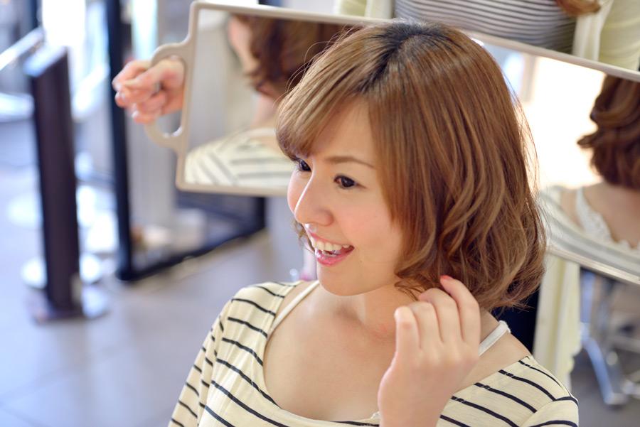 フリー写真 美容院で仕上がりをチェックする女性