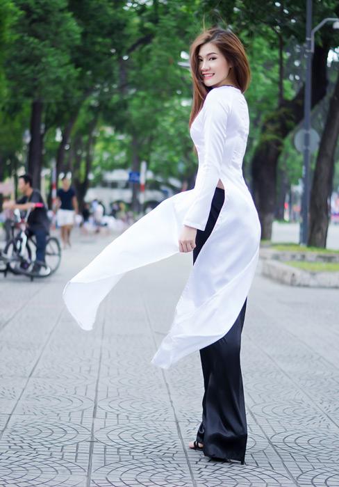 フリー写真 アオザイ姿で風に吹かれるベトナム人女性