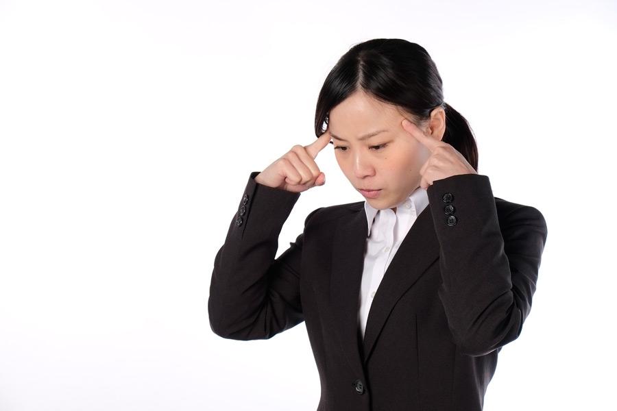 フリー写真 こめかみに指を当てて考え込んでいる女性社員