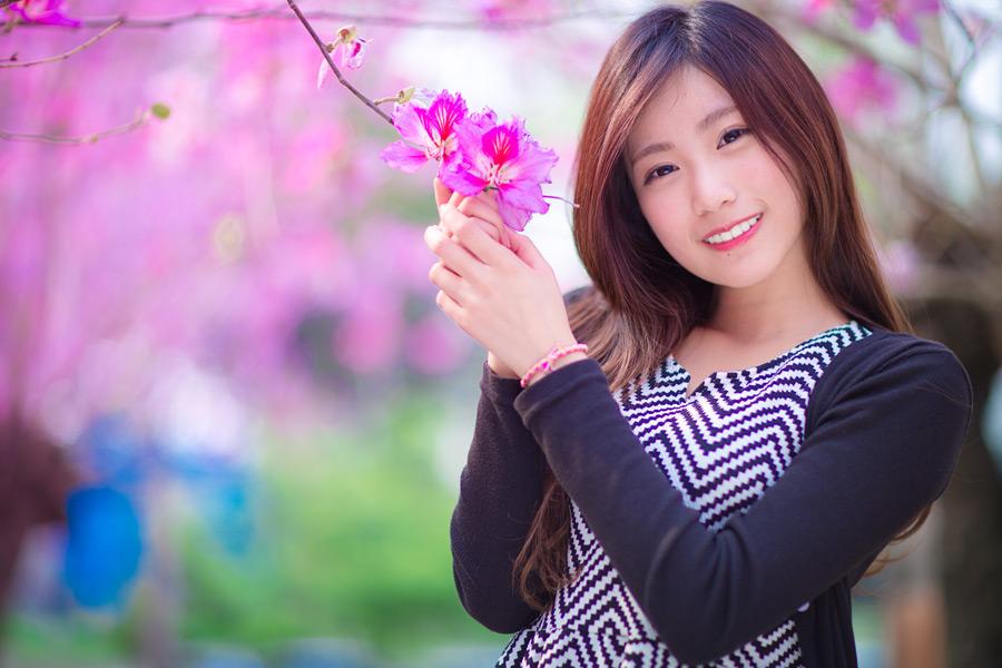 フリー写真 花の咲く枝と微笑む女性のポートレイト
