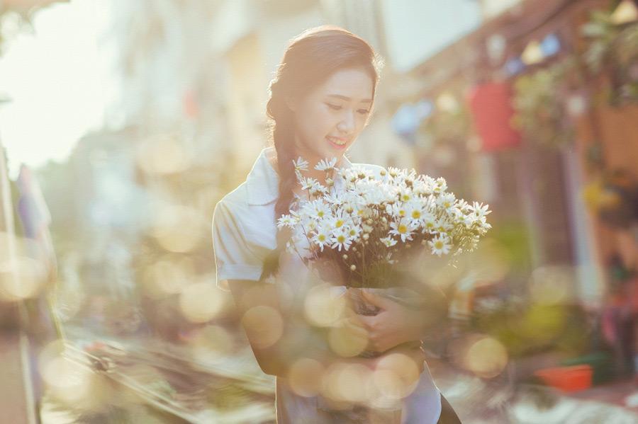 フリー写真 光の玉ボケと花束を抱える三つ編みの女子学生