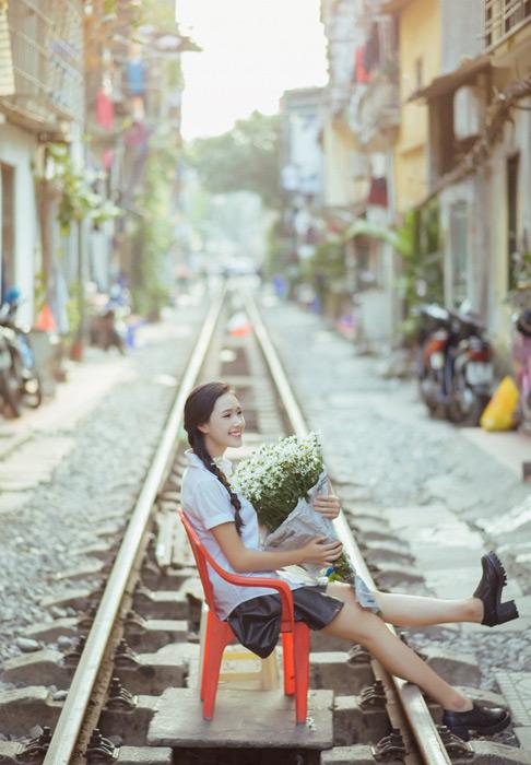 フリー写真 花束を抱えて線路の上に座る女子学生