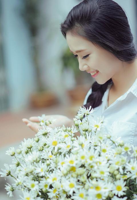フリー写真 白い花を手に乗せる女子学生のポートレイト