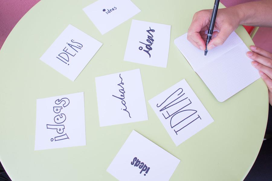 フリー写真 紙に書かれたアイデアと手帳に書く手