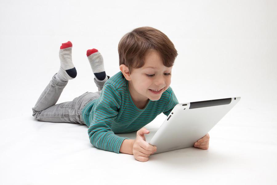 フリー写真 腹這いになってタブレットPCを使う男の子