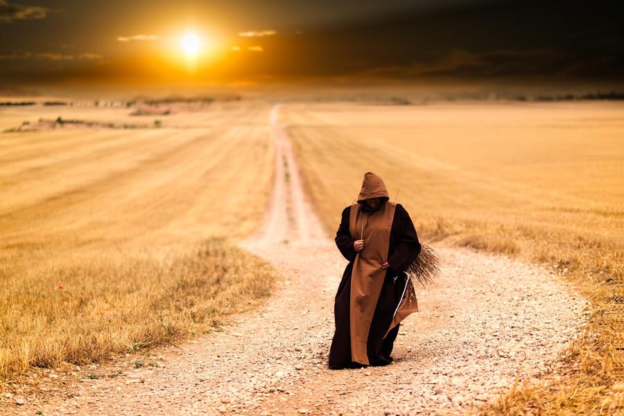 フリー写真 田舎道を歩くローブ姿の修道士