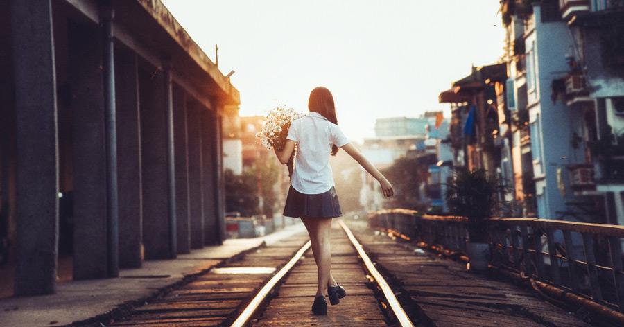 フリー写真 花束を抱えて歩く女子学生の後ろ姿