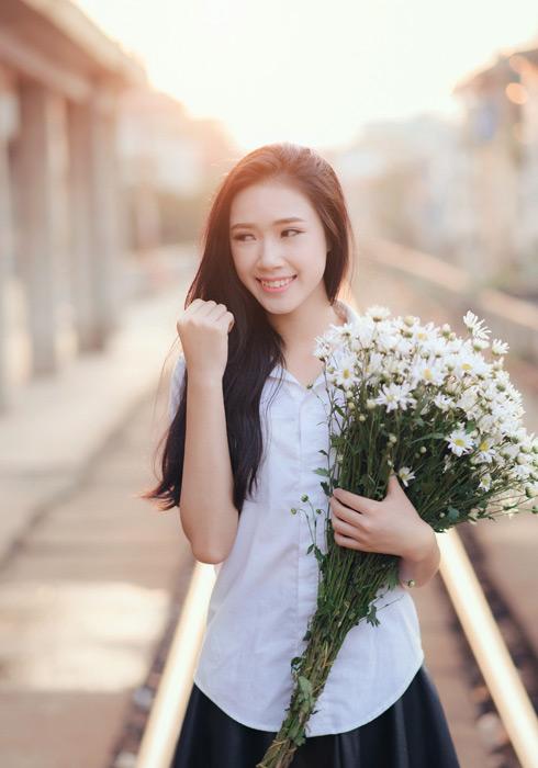 フリー写真 スクールブラウス姿で花束を抱える女子学生