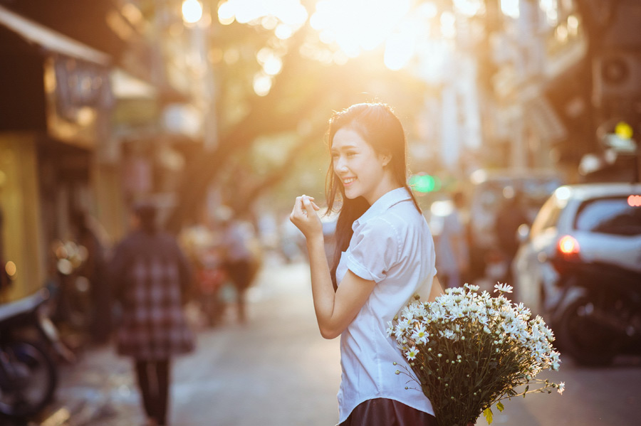 フリー写真 花束を持って街を歩く女子学生