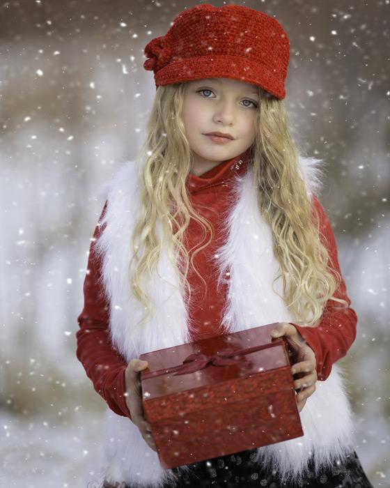 フリー写真 雪の中でプレゼント箱を持つ外国の女の子
