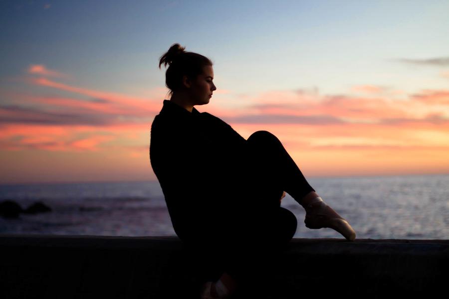 フリー写真 夕焼けとトウシューズを履いて座る外国人女性
