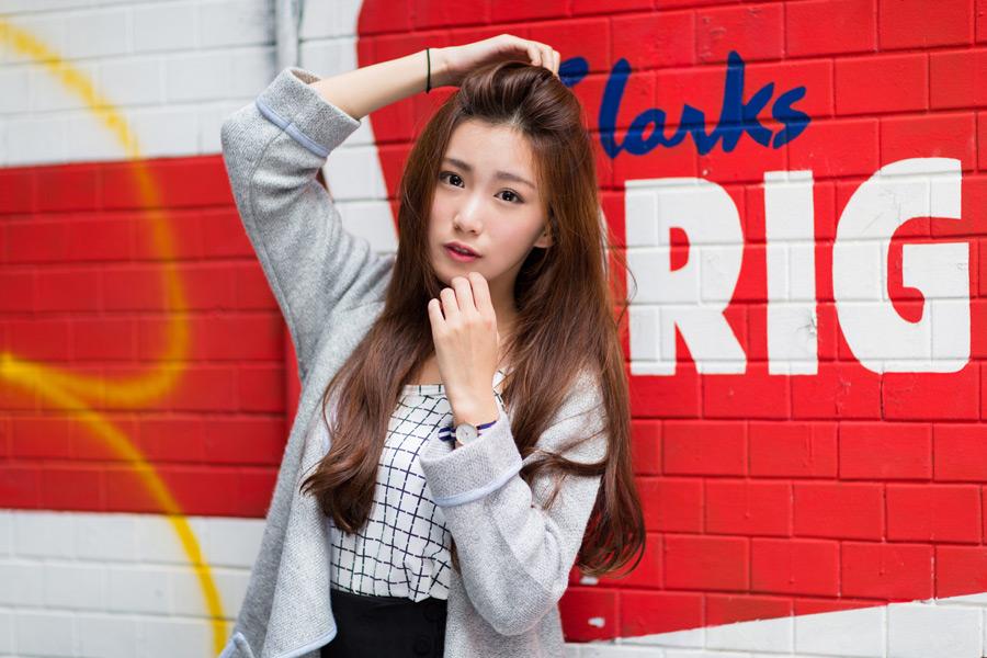フリー写真 壁の前で前髪をかき上げる女性ポートレイト