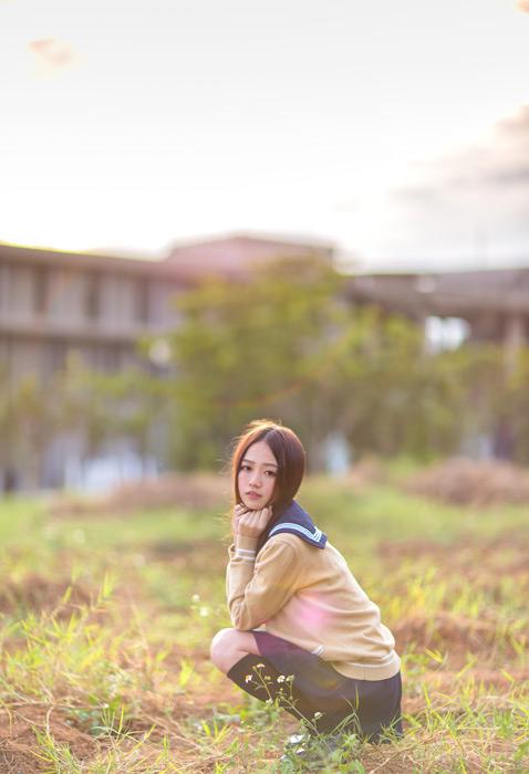 フリー写真 学生服姿で草むらにしゃがむ女子高生のポートレイト