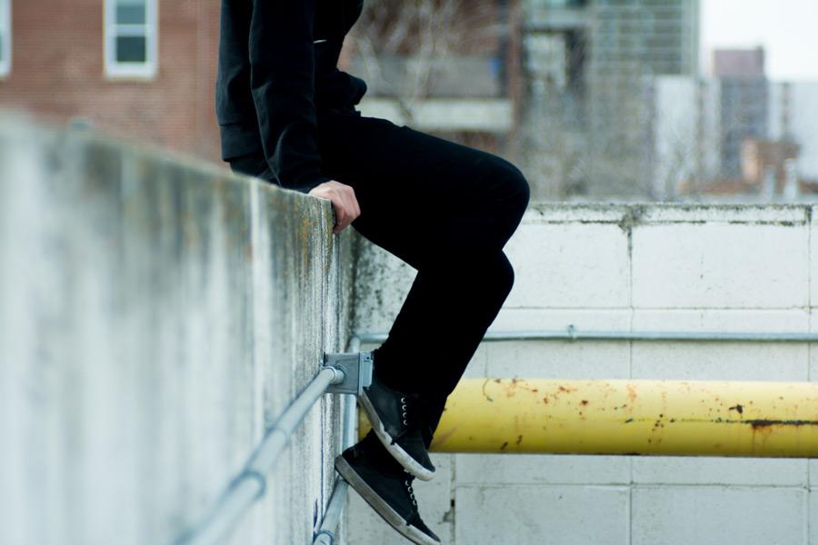 フリー写真 コンクリートの壁に座る人物