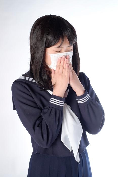フリー写真 マスクをしてくしゃみをしている女子高生