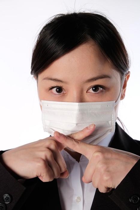 フリー写真 マスクをつけて指でバツを作る女性社員