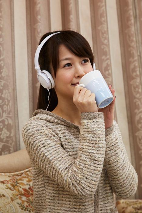 フリー写真 音楽を聴きながら飲み物を飲む日本人女性