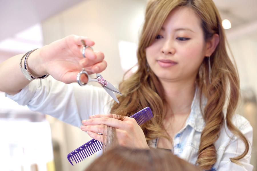 フリー写真 髪の毛をカットする美容師の女性