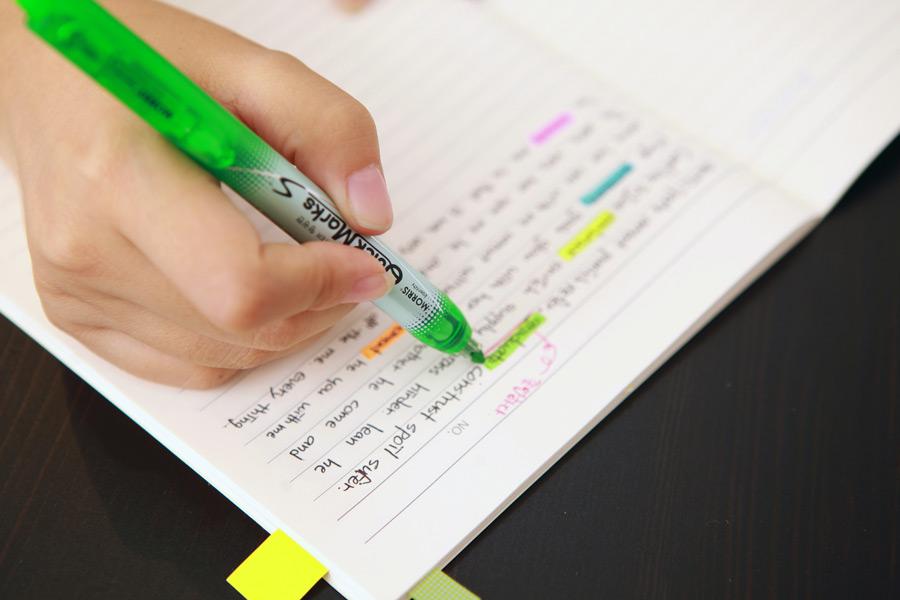 フリー写真 蛍光ペンでノートをマーキングしている手